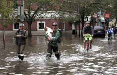 """""""Wading through water: A man carries his dog as people make their way out of the floodwaters in Hoboken, New Jersey today"""" #dogs"""
