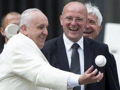 Pope Francis reaches out to catch a baseball thrown by someone in the crowd at the end of his weekly Wednesday General Audience in Saint Peter's Square, Vatican City