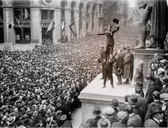 April 1918 Liberty War Bond Drive, Wall Street, New York.  Douglas Fairbanks hoisting up Charlie Chaplin, foot of George Washington's statue in front of the Sub-Treasury (now Federal Hall National Memorial). Throngs were crammed shoulder to shoulder as far as the eye could see.