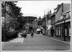 Datering tot: 1958-12-31 Beschrijving: De oostzijde van het Wilhelminaplein gezien vanaf de Groenelaan in de richting van de Dwarsstraat met rechts de Willem Brouwerstraat. Op de achtergrond de gashouders van de Gemeentelijke Gasfabriek en de Willem Brouwerschool.