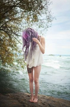 a girl standing at the beach, covering her face with her purple hair. beautyshot. love.