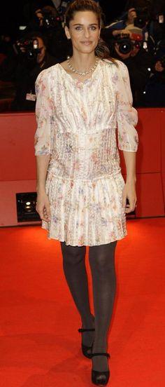 """A Amanda Peet (linda!), gravidíssima, estava em Berlim este final de semana promovendo seu filme """"Please Give"""". Ela usou um vestido floral e delicado (não parece Cris Barros?), mas eu achei que pesou um pouco a meia cinza e o sapato que ela escolheu… Vocês gostaram? Como teriam produzido?"""