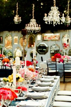 what inspiration! Mirrors on wall- reflect light, variety of blue cotton tablecloths, crystal chandeliers and lots of flowers, fruits and candles on the tables!