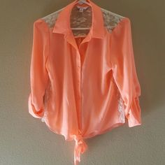 Blouse???? Peach blouse which ties at the bottom.  It is embossed with lace on the shoulders, top of the back & along the sides.  Super light with roll cuff sleeves.  Wrinkle resistant!  I have worn it twice.  It's 100% Polyester & 100% Lace.  There are no holes or damage anywhere? GREAT BUY????? Candie's Tops Button Down Shirts