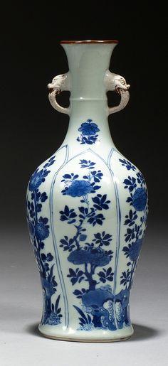 CHINE Époque KANGXI (1662-1722) Vase de forme balustre à col étroit en porcelaine décorée en bleu sous couverte dans des réserves en forme de pétales de rochers percés et fleuris de pivoines, deux anses en biscuit en forme de têtes de chimères à traces de laque or. Au revers de la base, la marque à la feuille d'acanthe. Hauteur : 26,5 cm