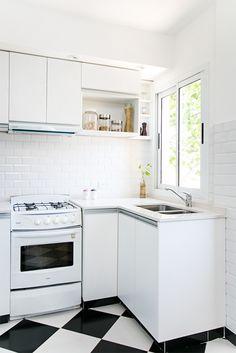 Cocina con piso tipo damero. Muebles de melamina blanca con manijas de aluminio. Mesadas de Silestone. Revestimiento sobremesada tipo subway tile biselados blancos.
