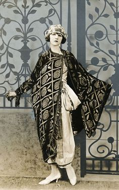 Fashion. An evening jacket in kimono model velor-Damase with asymetrical closure in a large checkered pattern, the evening dress of taffeta with large tie belt, the cap of silver lace. 1920. Location unknown. Series of 10 photos.