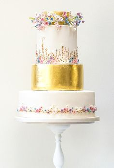 This whimsical cake design, created by Rosalind Miller Cakes, features two tiers covered in edible gold leaf, as well as tiny sugar wildflowers that look as if they were handpicked and fashioned into romantic flower crowns.