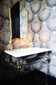 Stunning powder room boasts walls clad in Farrow & Ball Lotus Wallpaper framing a glass and brass washstand with two legs topped with white marble framing an oval sink paired with gold faucet kit under a gold bamboo mirror. Lotus Wallpaper, Bold Wallpaper, Bathroom Wallpaper, Amazing Wallpaper, Luxury Wallpaper, Mirror Bathroom, Gold Bathroom, Interior Desing, Home Interior