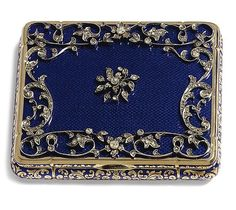 Antique vintage DIAMOND-SET GOLD AND ENAMEL BOX 18K, probably Hanau, third quarter of the 19th century of shaped rectangular form with shallow bombé sides, the lid enamelled in translucent blue and richly applied in rose diamonds with a central clematis flower within a wide openwork border of scrolling foliage and flowers, the sides similarly decorated in blue taille d'épargne,  Width 3-3/4 inches.