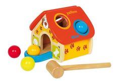 """Hier worden 4 kleurige houten kogels met de hamer in het dak """"verzonken"""" en ze rollen dan door de ingang er weer eruit. Zo worden de fijnmotoriek en de wereld van de kleuren spelenderwijze ontdekt! Een kleine leerklok toont de allerkleinsten met cijfers en vrolijke hondenmotieven """"hoe de tijd verstrijkt""""!"""