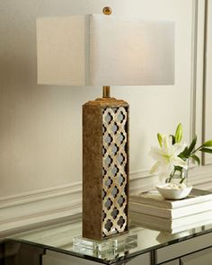 An oversized table lamp with the popular Moroccan inspired design made of capiz shell over top a mirrored back sits on a crystal base. Available at MERRIMAN DesignStudio.