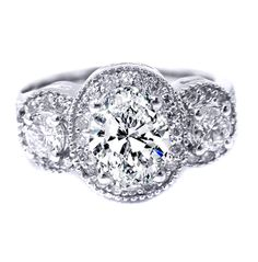 Love the vintage feel of this Three Stone Oval Diamond Halo Engagement Ring in 14K White Gold