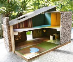 Hand crafted Mid Century Modern dollshouse. I have one of these. It's modular and comes packed within eachother. The box turns into a house. Got it MoMA.
