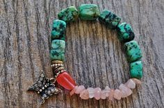 Contrast Green Turquoise and Rose Quartz and Pink Moon Stone. A Free flowing butterfly charm makes this bracelet soft and powerful. Bracelet shown is 7 1/2 inches longs and sturdy stretch cord. Please for your custom size message me your size. $45.00 USD