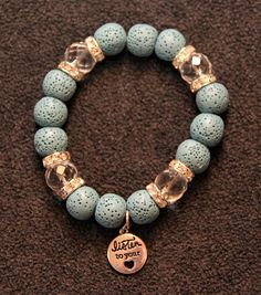 Beautiful diffuser bracelet made with blue lava beads and clear crystals as accents. Silver color charm says Listen to your Heart. Measures 7 1/2 and is made with stretch cord, so there is no clasp. Easy on and off. Put a drop or two of your favorite essential oil on each lava bead to add