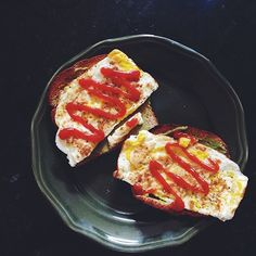 Ezekiel Bread (toasted) with a scrambled egg, mashed avocado, and ketchup.