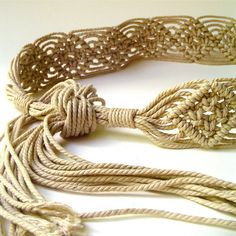 Great vintage boho woven macrame belt from the 1970s. This belt is macramed from what appears to be a neutral or wheat colored thick twisted cotton cord in a diamond pattern and is knotted at the end of the macramed section with long fringe at either end. The belt measures approximately 59 long by 2 wide. At its smallest it would fit a size 32 waist and is adjustable up to approximately a size 44 waist, by tying the fringe together at your desired length. The belt would fit a versatile…