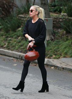 All star! Lady Gaga sported a funky football shaped handbag while visiting actor Bradley C...