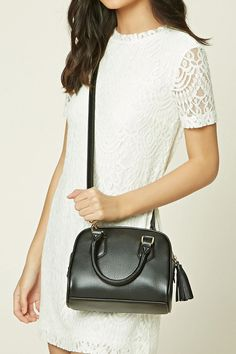 A faux leather mini satchel bag featuring top handles, a detachable crossbody strap, a top zip closure with a tasseled pull, and an interior zip pocket.