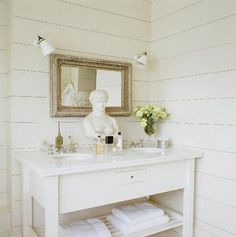 White washed cottage bathroom!   White wood paneling in bathroom! Love the minimalism of this space: White sink vanity with shelf, antique white washed wood framed mirror, white washed paneled walls and Greek bust! White paint wall colo
