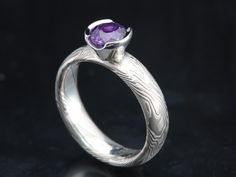 Purple sapphire in  a size 8 domed comfort fit etched ring 5mm wide in 14K palladium white gold and sterling silver in tight wood grain pattern with a platinum tapered half bezel setting