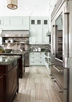 Such a dream kitchen! Gorgeous white cabinetry, stainless steel appliances, wood floors- so fresh and stylish!