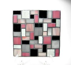 Beautiful stained glass mosaic four coaster set made using pink, gray and black colored glass pieces. The grout is gray and has been sealed for stain resistance and durability. These coasters could also be used as individual candle holders or displayed in a sunny window so that the light shines through! They also can be set close together and used as a large trivet! Each coaster is 4 in. x 4 in. The bottom of the coasters have little rubber feet to keep your furniture from scratching