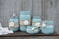 Shabby chic mason jar bathroom jar set. Hand painted in dusty blue, lightly distressed, wrapped with burlap, lace, tied with jute and ivory roses, finished with a protective coating. Metal soap dispen