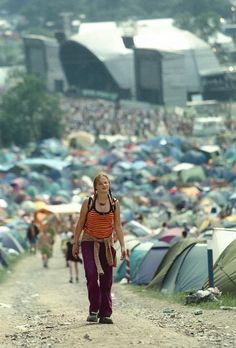 Woman walking on road with stage, Campsite at Glastonbury Festival, 1970