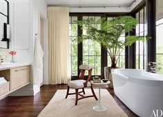 A Great Plains sheer fabric curtains the master bath, where a side table by Eero Saarinen for Knoll stands alongside the Duravit tub | archdigest.com