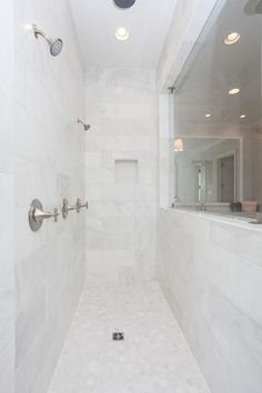 Long walk in shower displays honed white marble tiles in a narrow design featuring side by side shower heads.
