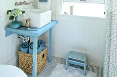 DIY sink stand: Build a simple table like this one by mounting an edge-glued panel over 2×2 legs reinforced with corner braces. Finish with a cheery, coordinating shade of paint. Install a drop-in basin or a statement-making vessel sink, like this one—just plan the stand's height accordingly. | Similar color to shown: Aura Bath & Spa Paint in Crisp Morning Air, @benjamin_moore