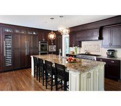 Dark cherry stained cabinets with an off white painted island - beautiful blend of colors and styles!