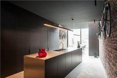 Edle offene Küche mit viel Edelstahl und offene Ziegelsteinen an der Wand
