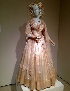 In 1940, Queen Victoria's white Honiton lace bridal gown made the white bridal gown popular with women everywhere. This Romantic Period bridal gown circa 1844 in cream silk satin is the oldest gown in the exhibit. It's rare to find an early Victorian wedding gown still intact.