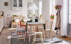 A light dining room with white stained dining table and chairs with space for 9 people.