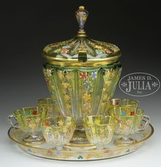 Comprised of a footed bowl with cover, tray and 7 footed cups. Chartreuse to clear decorated with etched grapevines. Each cup a quatrefoil form. SIZE: Bowl: h x d. Punch Bowl Set, Ludwig, Quatrefoil, Decanter, Vintage Kitchen, Grape Vines, Glass Art, Porcelain, Auction