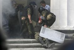 An injured national guard officer is carried away by comrades outside the parliament building in Kiev, Ukraine, August 31, 2015. Ukraine's parliament voted on Monday for constitutional changes to give separatist-minded eastern regions a special status - but divisions in the pro-Western camp and violent street protests suggested the changes would face a rougher ride to become law. REUTERS/Valentyn Ogirenko