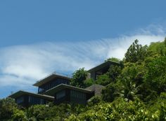 """FOUR SEASONS RESORT, SEYCHELLES ////// The new Four Seasons Resort at Petite Anse Bay, Mahe Island, rests very lightly upon the spectacular natural beauty and terrain of the site. A lightness achieved by perching slender stilts on existing boulders, by building around trees and outcrops. All the more joyful, the """"hidden"""" surprise of long span cantilevered structures, clinging to steep granite slopes, jutting out as dramatically as the vista of land, sea and skies beyond. #civil #structural"""