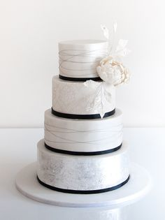 Black white and ivory wedding cake with flower silver leaf and ribbon - 4 Tier