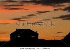 Last house: Silhouette of a cottage against orange skies - stock photo