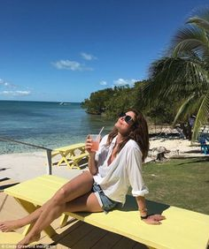Tropical getaway: Cindy Crawford, 51, shared a photo to her Instagram Sunday showing her flaunting her long legs in a pair of tiny denim shorts as she relaxed against a stunning backdrop