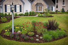 A more dramatic option is to create an island of color in the middle of the lawn. It breaks up a wide expanse with a colorful focal point.