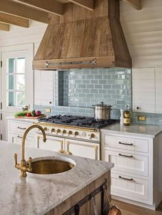Cottage kitchen Wood hood and blue subway tiles.