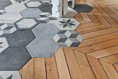 Voici une transition de toute beauté réalisée par Ouest Home. Le grès cérame graphique imitation carreaux de ciment de la cuisine s'incruste dans le parquet. Une liaison parfaite entre des lames de bois anciennes et un carrelage tendance et moderne.