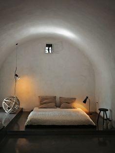 Riabitare un trullo. Il letto nella Lumia è a contatto con la terra come nell'antica tradizione contadina. Lampade: Parentesi di Flos e originale degli anni '60.