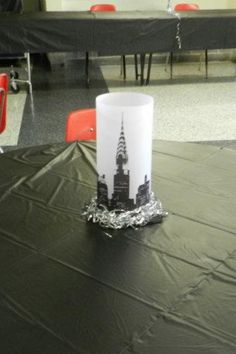 Table center pieces...faux frosted glass candle holders made from vellum. I just found a good cityscape silhouette and printed it on the vellum. Used sticky dots to close up the 'vase' and used battery operated mini candles that flickered. I hot glued the cylinder on a black cardboard square and used silver tinsel to hide the glue.