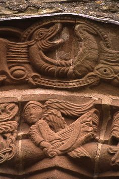 File:Kilpeck Angel carving. from the exquisite Romanesque church This detail is found at  the centre of the arch of the south door and shows a flying angel and a curled serpent Photo by Simon Garbutt