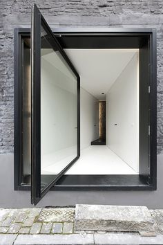 12 Pivot Doors Leading To Patios: Architectural firm Graux & Baeyens added an oversized, modernist pivot door encased in black to this 19th century house located by the old city harbor docks of Ghent, Belgium. The project started by stripping the dilapidated house of all excess.